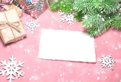 圣诞节在浅粉红色的桌的贺卡与雪花,礼物,杉树分支 平的位置样式 免版税库存图片