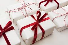 圣诞节在白皮书和装饰红色绳索丝带包裹的礼物盒大理石的表面上 等量 关闭 免版税库存图片