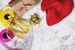 圣诞节在白色大理石桌上的礼物准备与拷贝空间 有礼物盒和五颜六色的丝带的红色圣诞老人帽子 免版税库存照片