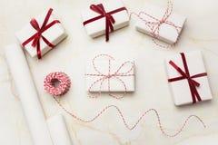 圣诞节在白色工艺纸和装饰红色丝带包裹的礼物盒大理石的表面上 平的位置,顶视图 库存照片
