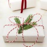 圣诞节在白色工艺纸和装饰红色绳索丝带包裹的礼物盒大理石的表面上 关闭 免版税图库摄影