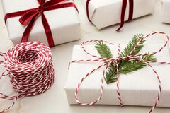 圣诞节在白色工艺纸和装饰红色绳索丝带包裹的礼物盒大理石的表面上 关闭 图库摄影