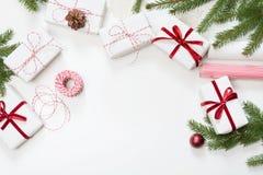 圣诞节在白色工艺纸和装饰红色绳索丝带包裹的礼物盒白色表面上 平的位置 顶视图 图库摄影