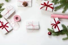 圣诞节在白色工艺纸和装饰红色绳索丝带包裹的礼物盒白色表面上 平的位置 顶视图 库存照片