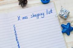 圣诞节在白色木背景的购物单 假日deco 免版税库存图片