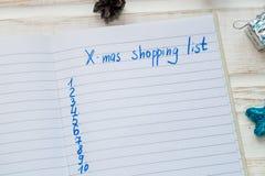 圣诞节在白色木背景的购物单 假日deco 免版税图库摄影