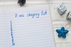 圣诞节在白色木背景的购物单 假日deco 库存图片
