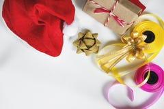 圣诞节在白色桌上的礼物准备与拷贝空间 有礼物盒和五颜六色的丝带的红色圣诞老人帽子 图库摄影