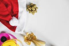 圣诞节在白色桌上的礼物准备与拷贝空间 有礼物盒和五颜六色的丝带的红色圣诞老人帽子 库存照片