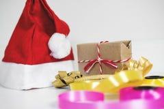 圣诞节在白色桌上的礼物准备与 有礼物盒和五颜六色的丝带的红色圣诞老人帽子 库存图片