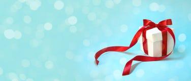 圣诞节在白色箱子的礼物` s有在浅兰的背景的红色丝带的 新年假日构成横幅 复制空间 免版税库存照片
