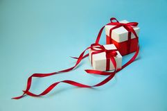 圣诞节在白色箱子的礼物` s有在浅兰的背景的红色丝带的 新年假日构成 复制空间 免版税库存照片