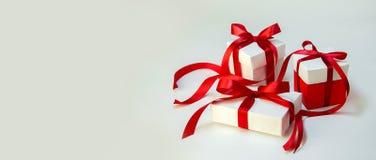 圣诞节在白色箱子的礼物` s有在轻的背景的红色丝带的 新年假日构成横幅 复制您的文本的空间 免版税库存照片