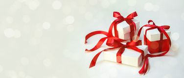 圣诞节在白色箱子的礼物` s有在轻的背景的红色丝带的 新年假日构成横幅 复制您的文本的空间 库存照片