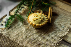 圣诞节在粗麻布布料的肉馅饼与杉树分支和肉桂条,油罐顶部角钢视图 免版税库存图片