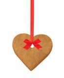 圣诞节在红色丝带的心脏曲奇饼与在白色隔绝的弓 免版税库存图片