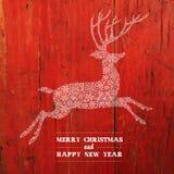 圣诞节在红色板条纹理的鹿剪影 免版税库存照片