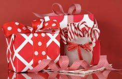 圣诞节在红色背景的礼物盒,与条纹棒棒糖 免版税库存照片