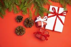圣诞节在红色背景的礼物礼物 有丝带弓的简单,经典,红色和白色被包裹的礼物盒和 图库摄影