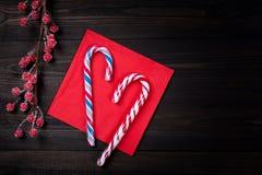 圣诞节在红色餐巾的棒棒糖用在黑暗的木桌上的冷冻红色莓果 与拷贝空间的圣诞节或新年背景 免版税库存照片