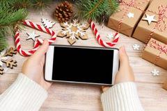 圣诞节在线购物 女性买家做命令在智能手机屏幕有拷贝空间的 妇女买xmas前夕的礼物,坐 图库摄影