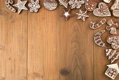 圣诞节在老木桌上的姜饼曲奇饼行  免版税库存图片