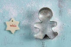 圣诞节在葡萄酒水色蓝色木桌上的曲奇饼切削刀 免版税库存图片