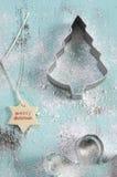 圣诞节在葡萄酒水色蓝色木桌上的曲奇饼切削刀 免版税库存照片