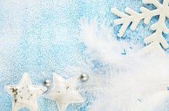 圣诞节在蓝色和白色多雪的背景戏弄 星、雪花和羽毛 免版税库存图片