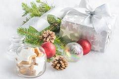 圣诞节在银色包装纸的礼物盒在白色蓬松背景 充分瓶子星曲奇饼和圣诞节装饰 免版税图库摄影