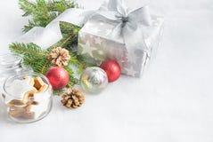 圣诞节在银色包装纸的礼物盒在白色蓬松背景 充分瓶子星曲奇饼和圣诞节装饰 库存照片
