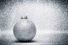 圣诞节在银色闪烁背景的玻璃球装饰 库存照片