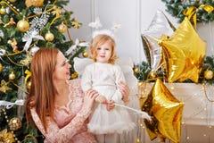 圣诞节在结构树附近的女儿母亲 库存图片