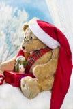 圣诞节坐在冬时的窗口的玩具熊 免版税库存图片