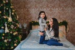 圣诞节坐床和拥抱小女儿的愉快的微笑的母亲家庭画象近对圣诞树在家 免版税库存照片