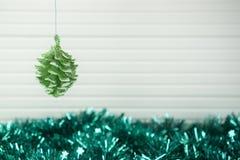圣诞节垂悬与闪亮金属片和白色木背景的xmas装饰的摄影图象绿色闪烁杉木锥体雪中看不中用的物品 库存图片