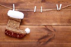 圣诞节垂悬在棕色木背景、快活的xmas和新年好卡片,拷贝空间,顶视图的长袜袜子 免版税库存图片