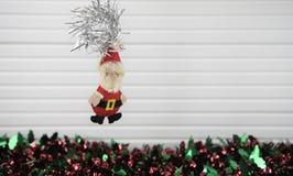 圣诞节垂悬手工制造圣诞老人红色绿色闪亮金属片和白色木背景的xmas装饰的摄影图象 免版税库存照片