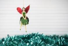 圣诞节垂悬有绿色闪亮金属片和白色木背景的老木神仙的xmas装饰的摄影图象 免版税图库摄影