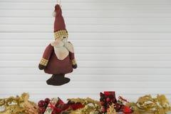 圣诞节垂悬老葡萄酒手工制造圣诞老人玩具的xmas装饰的摄影图象有金子在白色木头的xmas背景 免版税库存图片