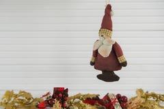圣诞节垂悬老葡萄酒手工制造圣诞老人玩具的xmas装饰的摄影图象有金子在白色木头的xmas背景 免版税库存照片