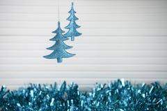 圣诞节垂悬蓝色闪烁xmas树和蓝色闪亮金属片和白色木背景的xmas装饰的摄影图象 库存照片