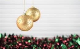 圣诞节垂悬金子与色的闪亮金属片和白色木背景的闪烁中看不中用的物品的xmas装饰的摄影图象 库存照片