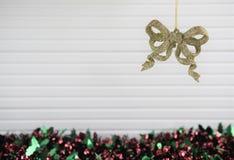 圣诞节垂悬金子闪烁与闪亮金属片和白色木背景的弓中看不中用的物品的xmas装饰的摄影图象 免版税库存图片