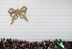 圣诞节垂悬金子闪烁与闪亮金属片和白色木背景的弓中看不中用的物品的xmas装饰的摄影图象 免版税库存照片