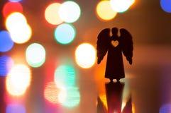 圣诞节天使剪影与孔的以心脏的形式 库存照片