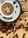 圣诞节天使,拿铁咖啡艺术设计,顶视图 烤咖啡豆在木桌上驱散了在茶碟的一个杯子旁边 免版税图库摄影