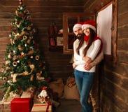 圣诞节夫妇在新年装饰的一个农村木房子里 免版税库存照片
