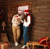 圣诞节夫妇在演奏玩具的农村木房子里 库存图片
