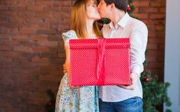 圣诞节夫妇当前共享 在家拥抱和拿着红色礼物盒有装饰的年轻家庭 库存照片